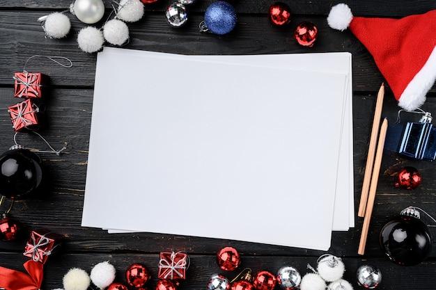 Papier avec jeu de jouets de décoration d'arbre de noël, vue de dessus à plat, avec espace de copie pour le texte, sur fond de table en bois noir