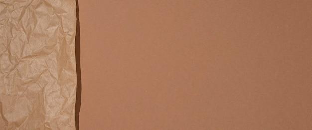 Papier kraft froissé sur fond de carton marron. bannière.
