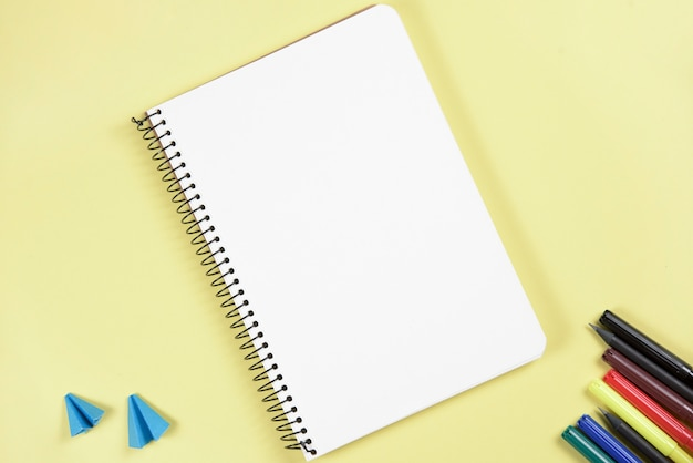 Papier kraft plié et feutre près du bloc-notes à spirale vierge sur fond jaune