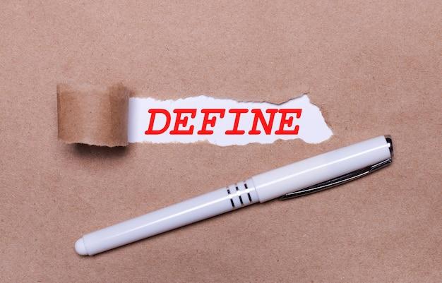 Sur papier kraft, un stylo blanc et une bande de papier blanc avec le texte define.