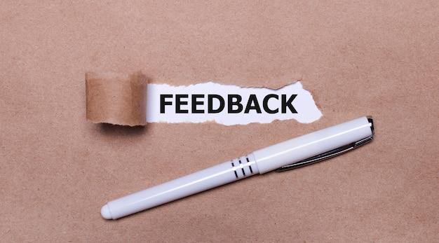 Sur papier kraft, un stylo blanc et une bande de papier blanc avec le texte feedback.