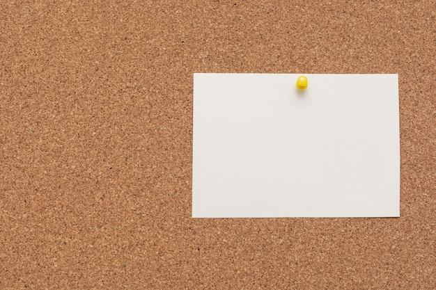 Papier à lettres dépouillé avec punaise sur tableau en liège