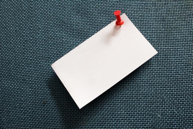 Papier à lettres et punaise rouge dans un tableau de liège bleu avec espace de copie