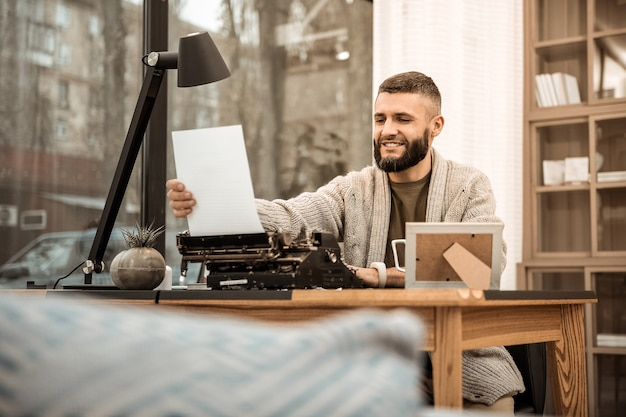 Papier de machine à écrire. l'écrivain barbu souriant étant satisfait de son travail alors qu'il était assis dans un long cardigan tricoté