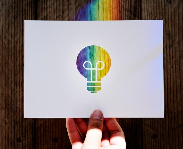 Papier de main tenant l'ampoule découpant avec la lumière de prisme