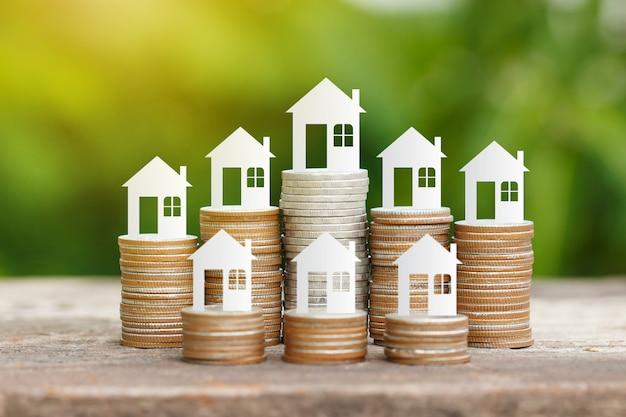 Papier de la maison sur la pile de pièces pour économiser pour acheter une maison