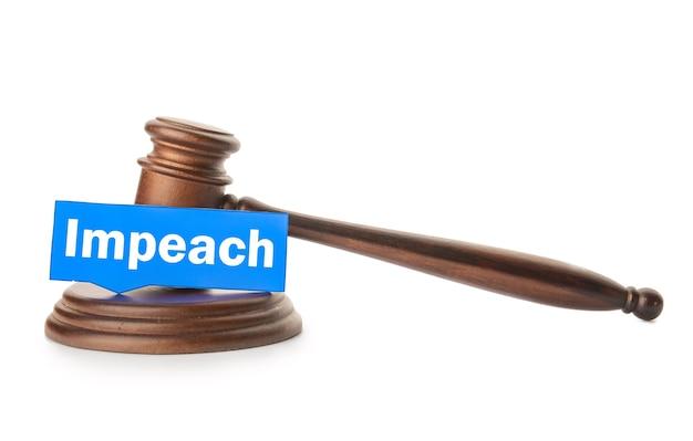 Papier avec mot impeach et juge gavel sur mur blanc