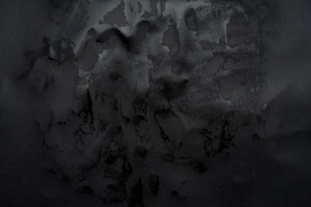 Papier noir humide collé au mur. texture de papier humide.