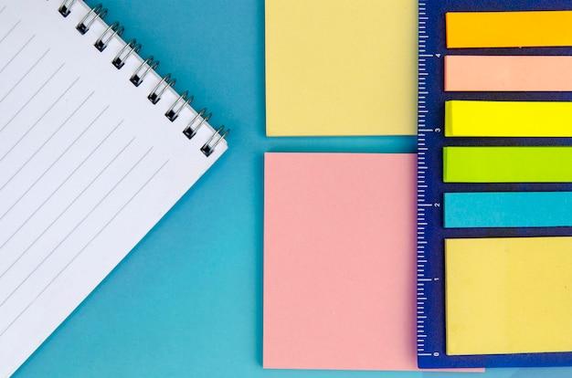 Le papier note des couleurs différentes. retour à l'école. fournitures de bureau d'en haut