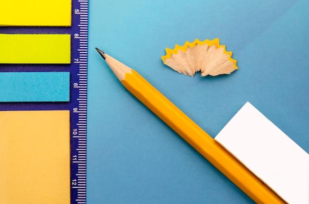 Papier notes de couleurs différentes, crayon de bois jaune et caoutchouc.