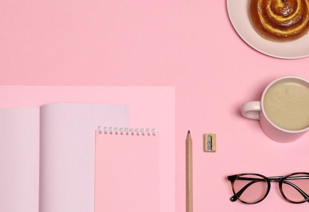 Papier à notes roses, crayon en bois, taille-crayon, tasse à café, gâteau sur fond rose