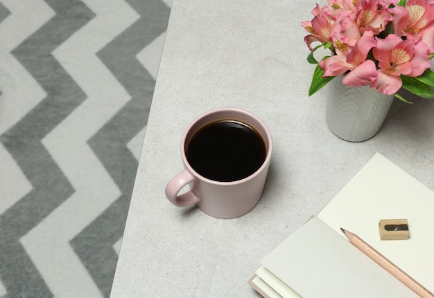 Papier à notes roses, crayon, tasse à café, fleurs posées sur une table en pierre grise