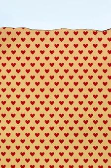 Papier orange avec petits coeurs rouges