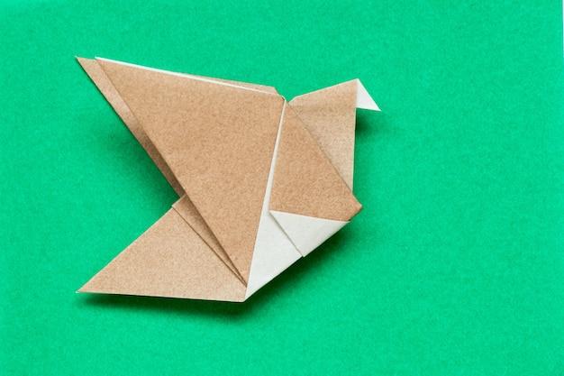 Papier origami brun en forme d'oiseau en vol sur fond vert