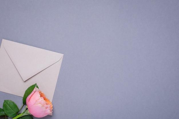 Papier peint gris avec enveloppe cadeau et rose rose