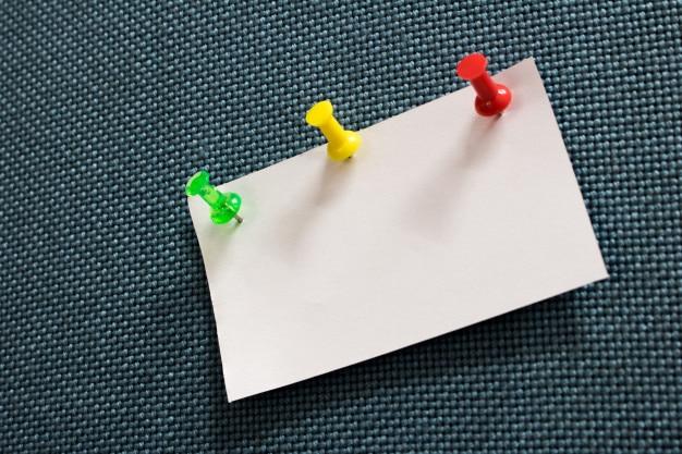 Papier pour notes en gros plan et nombreuses couleurs épingle dans un tableau de liège bleu avec espace de copie