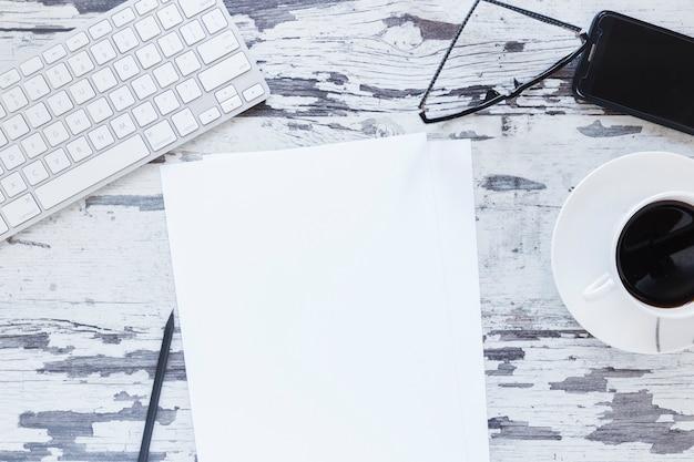 Papier près d'appareils électroniques et d'une tasse à café