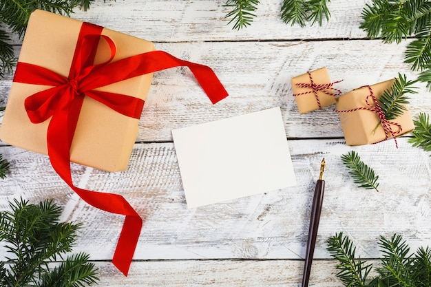 Papier près de brindilles de sapin, stylos et boîtes à cadeaux