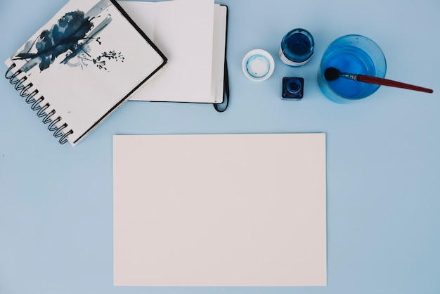 Papier près des carnets de croquis et de la peinture