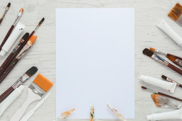 Papier près des pinceaux, des tubes de peinture et des couteaux