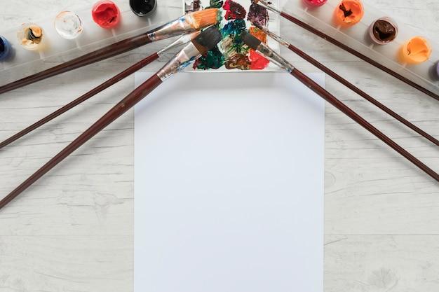 Papier près de pots de gouache et de pinceaux