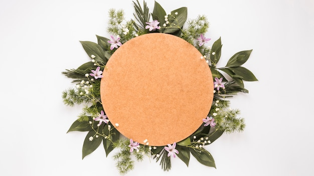 Papier rond sur des branches de plantes vertes et des fleurs