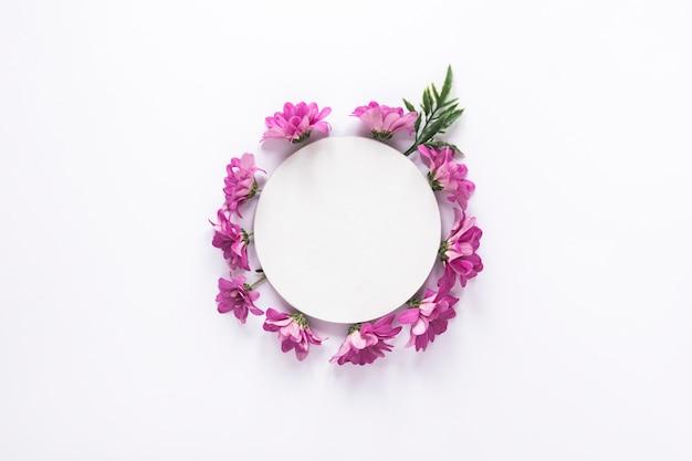 Papier rond sur fleurs violettes sur table