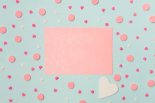 Papier rose entre symboles de coeurs et ronds décoratifs