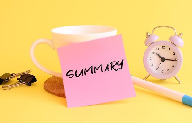 Papier rose avec le résumé du texte sur une tasse blanche. horloge, stylo sur fond jaune. concept design.