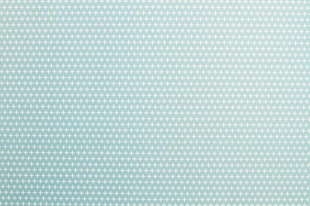 Papier avec des signes plus blancs sur fond bleu clair