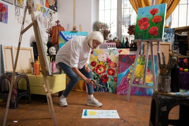 Papier sur le sol. artiste créatif et talentueux âgé saupoudrant de la peinture sur du papier allongé sur le sol