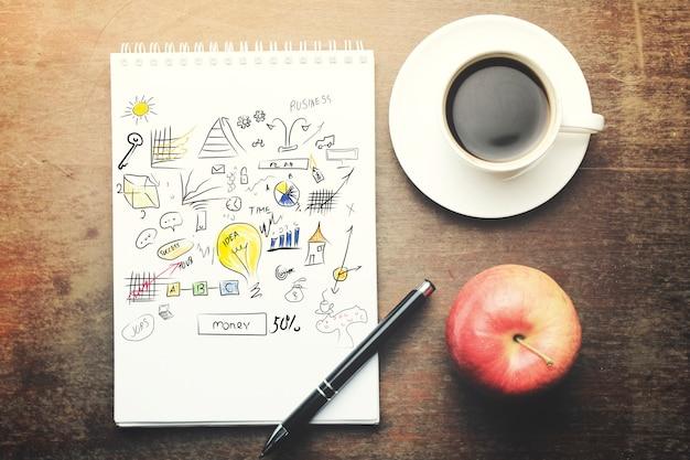 Papier avec stylo, tasse à café et pomme rouge sur table en bois