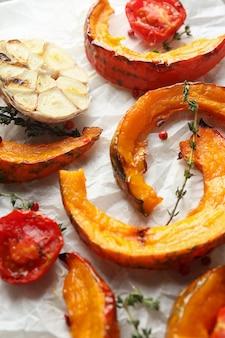 Papier sulfurisé avec citrouille au four et épices, gros plan.