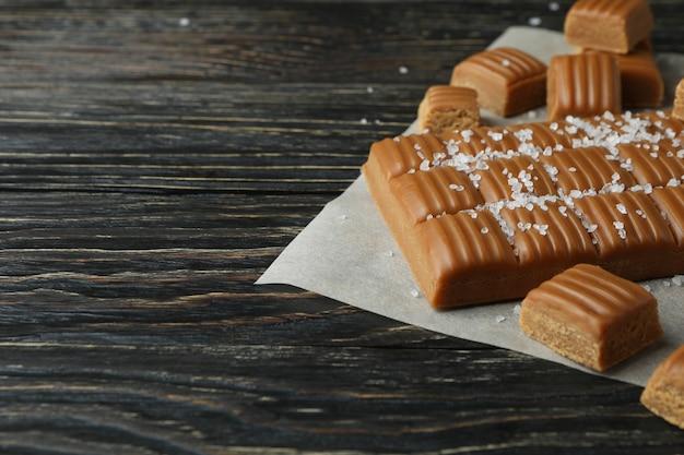 Papier sulfurisé avec des morceaux de caramel salé sur fond de bois