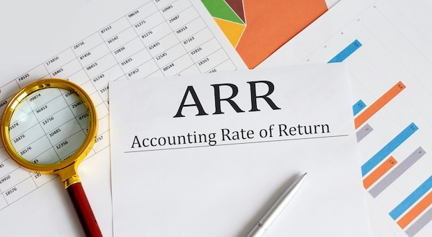 Papier avec taux de rendement comptable arr sur une table avec graphiques, stylo et loupe
