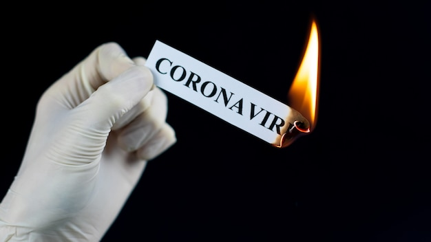 Le papier avec le texte coronavirus brûle dans la main.