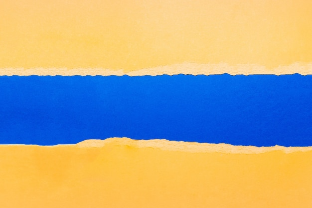 Papier texturé jaune déchiré naturel sur couleur bleue.