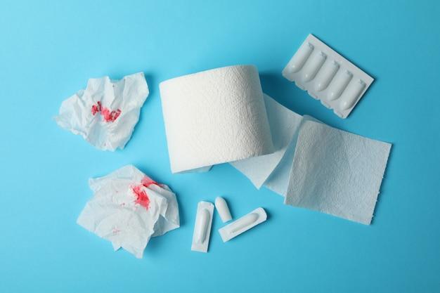 Papier toilette, bougies et papier avec du sang sur bleu, vue de dessus