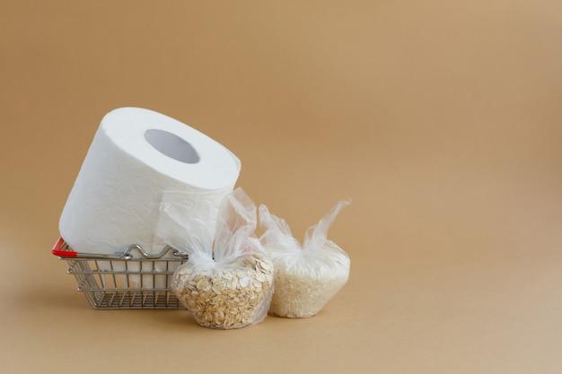 Papier toilette dans un panier d'épicerie et diverses céréales dans de petits sacs en plastique riz et flocons d'avoine