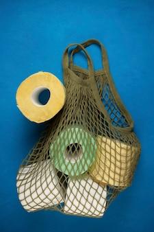 Papier toilette multicolore dans un sac à cordes sur fond bleu