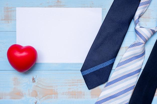 Papier vide avec des cravates bleues et une forme de coeur rouge sur bois