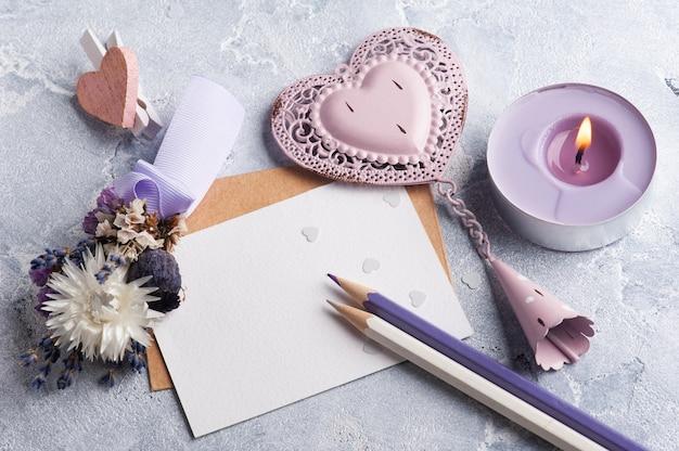Papier vide et enveloppe kraft avec coeur décoratif rose et fleurs sèches. maquette de mariage sur table grise