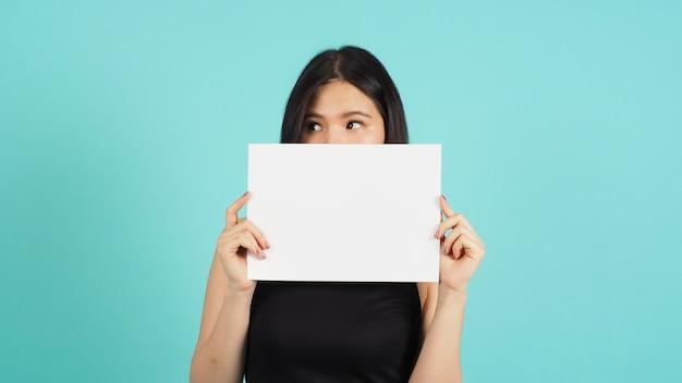 Papier vide vierge dans la main d'une femme asiatique sur fond vert menthe ou bleu tiffany.