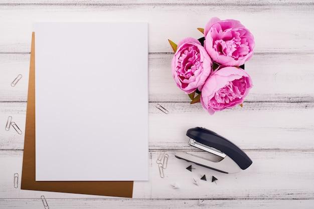 Papier vierge sur le bureau en bois avec fleur et ciseaux