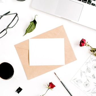 Papier vierge, enveloppe artisanale, roses rouges, ordinateur portable, café sur une surface blanche
