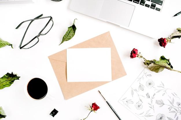 Papier vierge, enveloppe de métier, roses rouges, ordinateur portable, vue de dessus de café