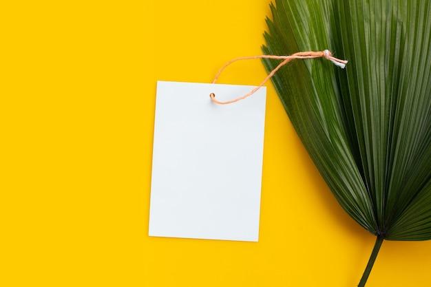 Papier vierge avec des feuilles de palmiers tropicaux sur une surface jaune. copier l'espace