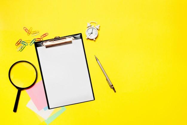Papier vierge avec des fournitures de bureau sur fond jaune.