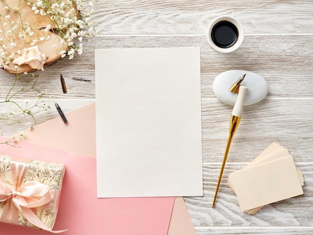 Papier vierge pour invitation ou lettre sur fond en bois blanc avec stylo de calligraphie et encre. pile de cartes de visite. vue depuis le sommet.