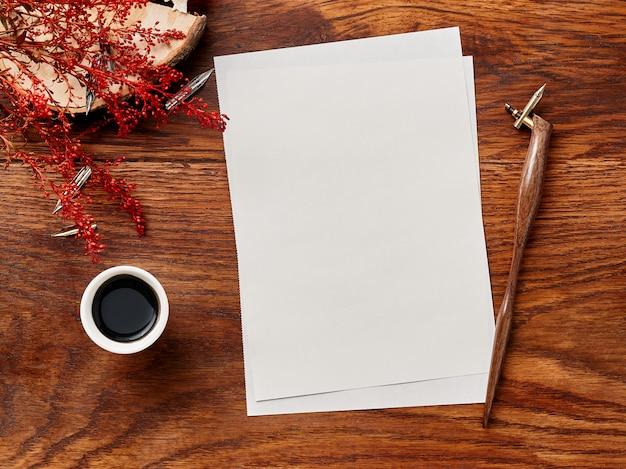 Papier vierge pour invitation ou lettre sur fond en bois avec stylo de calligraphie et encre. vue depuis le sommet.